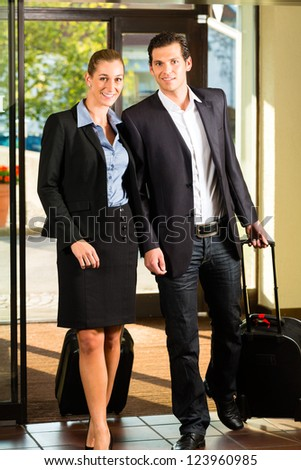 Business people arriving at Hotel with suitcases - stock photo