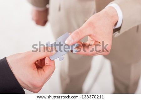 Business people assembling jigsaw puzzle. Teamwork. On white background.
