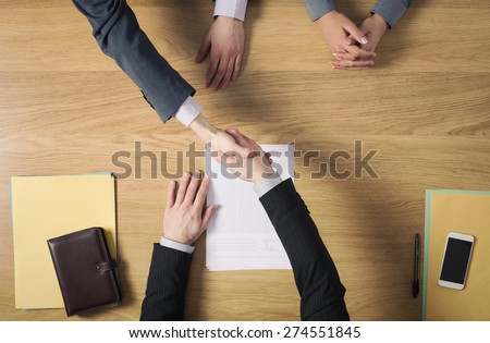 Business people at office desk handshaking after signing an agreement, hands top view, unrecognizable people - stock photo