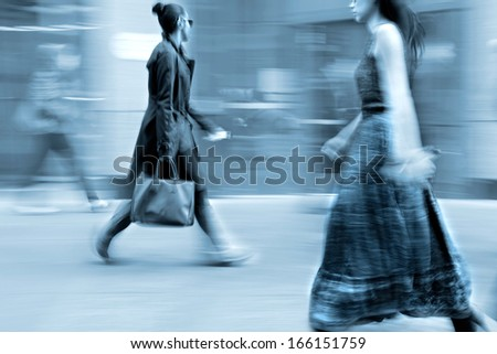 Business people at rush hour walking in the street, in the style of motion blur and blue tonality  - stock photo