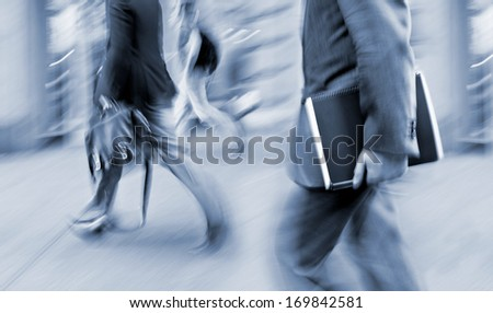 Business people at rush hour walking in the street, in the style of motion blur and blue tonality