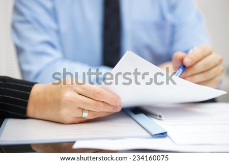 Business people at the office discussing and analyzing document - stock photo