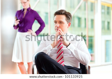 Business people - boss and secretary in office, he is sitting and she makes a phone call - stock photo