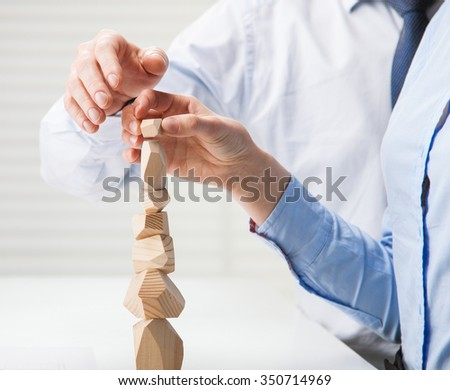 Business people building wooden tower (Japanese game tumi-ishi), illustrating concept of business success, cooperation, achievement and self-control - stock photo