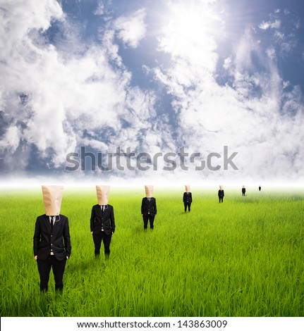 Business People businessman put  paper bag on head stand per row on grass field - stock photo