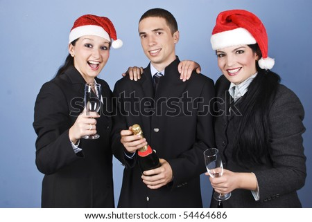 Business people celebrate Christmas with champagne and wearing Santa hats and laughing together on blue background - stock photo