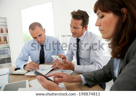Business people checking on smartphone to book meeting time