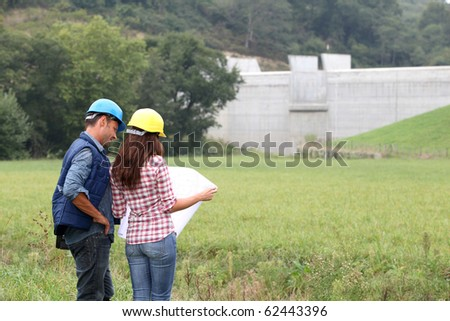 Business people checking plan on construction site - stock photo