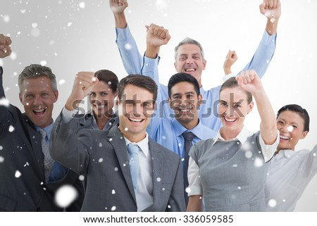 Business people cheering in office against snow - stock photo