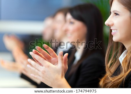 Business people clapping hands during a conference