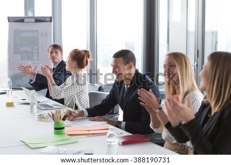Business people clapping hands during the meeting in modern office. - stock photo