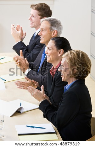 Business people clapping in meeting - stock photo