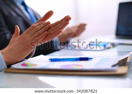 Business people clapping, sitting on the desk - stock photo