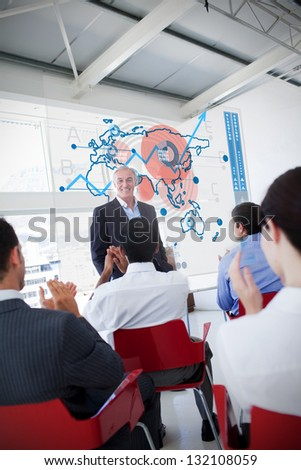 Business people clapping stakeholder standing in front of blue map diagram interface in a meeting