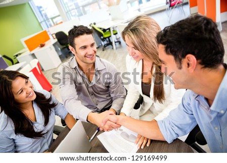 Business people closing a deal and handshaking at the office - stock photo
