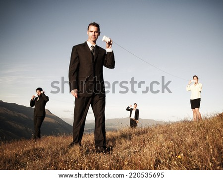 Business people communicate through the paper cup phone outdoors. - stock photo