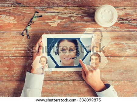 business, people, communication and technology concept - close up of hands pointing finger to tablet pc computer screen with helpline operator image, coffee cup and eyeglasses on table