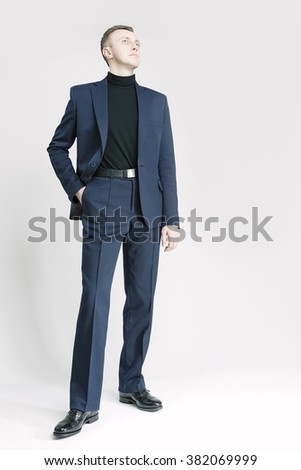 Business People Concepts and Ideas. Elegant Caucasian Businessman in Blue Suite Posing Against White. Vertical Shot - stock photo