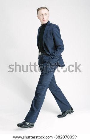Business People Concepts and Ideas. Portrait of Caucasian Business Man Marching Against White. Vertical Image Orientation - stock photo