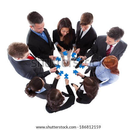 Business people connecting puzzle pieces over white background - stock photo