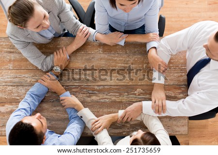 business, people, cooperation and team work concept - close up of creative team sitting at table and holding hands in office - stock photo