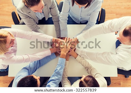 business, people, cooperation and team work concept - close up of creative team sitting at table and holding hands on top of each other in office - stock photo