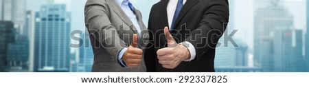 business, people, cooperation, success and gesture concept - businessman and businesswoman showing thumbs up over city background - stock photo