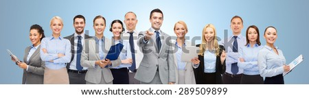 business, people, corporate, teamwork and office concept - group of happy businesspeople pointing at you over blue background - stock photo