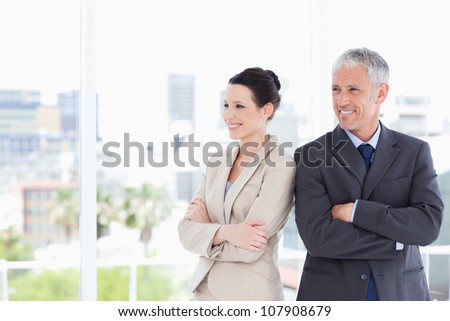 Business people crossing their arms while looking towards the side and smiling - stock photo