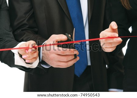 Business people cutting a red ribbon with a pair of scissors, closeup - stock photo