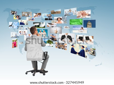 business, people, design and choice concept - businessman sitting in office chair and looking at different images over blue background from back - stock photo