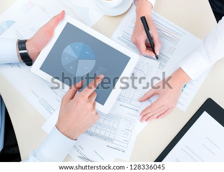 Business people developing a business project and analyzing market data information on a modern digital tablet computer. Top view photo shoot. - stock photo