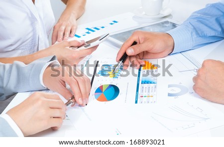 business people discuss meeting targets, sitting at the business table with documents - stock photo