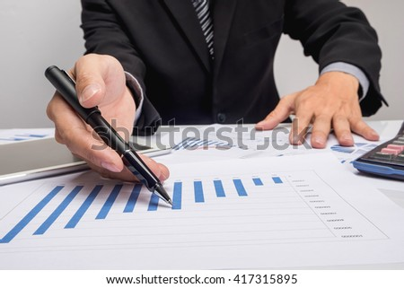 Business people discussing financial charts - closeup shot of hands over table.