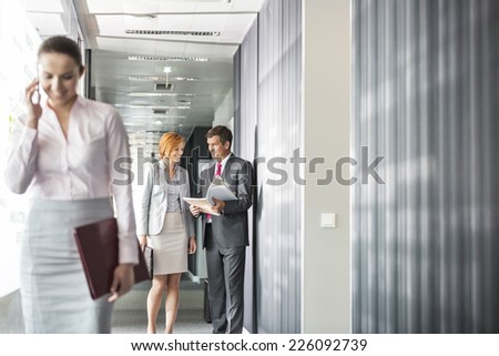 Business people discussing in corridor with colleague using cell phone in foreground - stock photo
