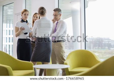 Business people discussing over documents in lobby - stock photo