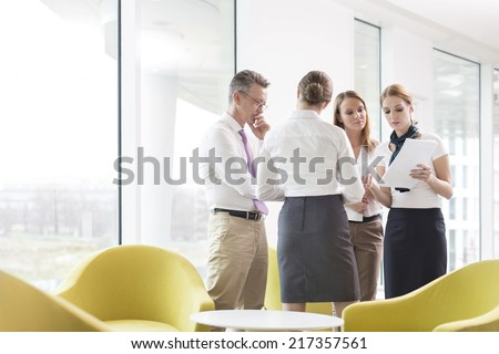 Business people discussing over documents in office lobby - stock photo