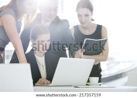 Business people discussing over laptop in office cafeteria - stock photo