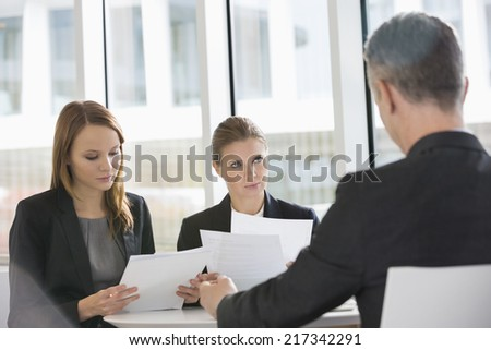 Business people discussing paperwork in office cafeteria - stock photo