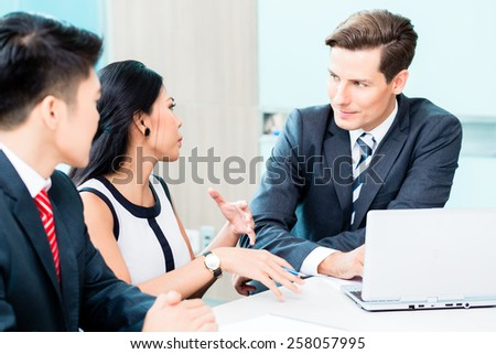 Business people discussing project in office, Asian and European executives - stock photo