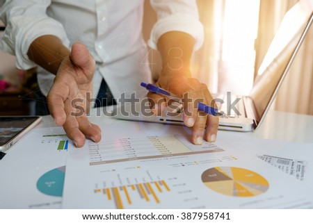 Business people discussing the charts and graphs on desk. - stock photo