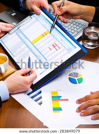 Business people discussing the charts and graphs showing the results of their successful teamwork - stock photo