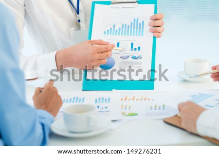 Business people discussing the results of their work presented in charts and graphics