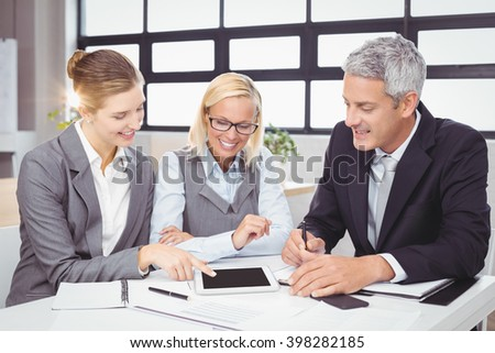 Business people discussing with client over digital tablet at desk in office - stock photo