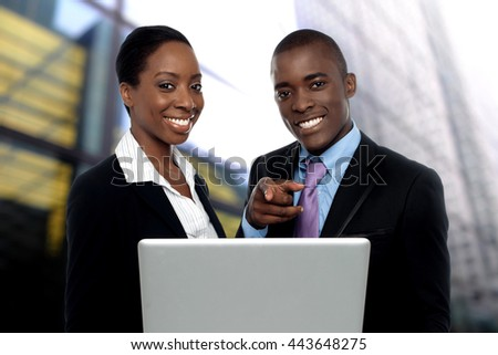 Business people discussing with laptop outside office - stock photo
