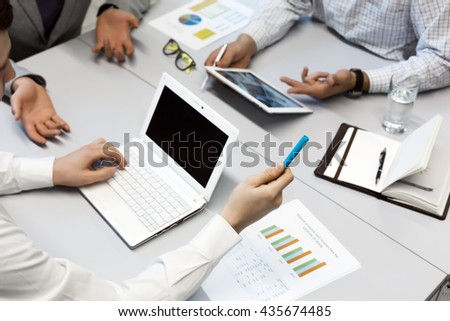 Business People discussion at Table using variety of electronic Devices on grey Office Table Computer, Tablet, printed Paper Charts