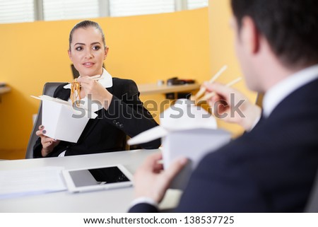 Business people eating Chinese food during lunch break in the office - stock photo