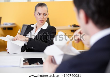 Business people eating Chinese food in the office and chatting - stock photo