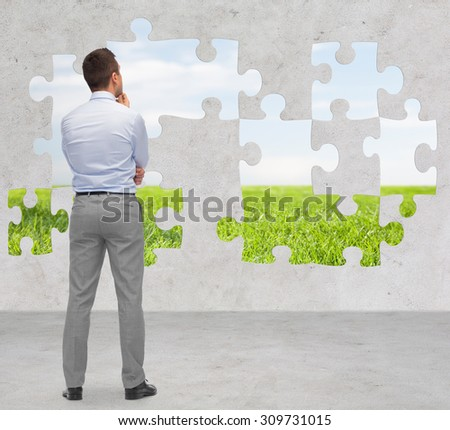 business, people, ecology and strategy concept - businessman thinking from back over puzzle with natural landscape and concrete room background - stock photo