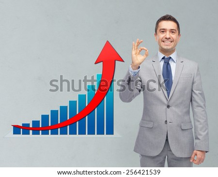 business, people, economics and financial success concept - happy smiling businessman in suit ok hand sign with growth chart over gray background - stock photo